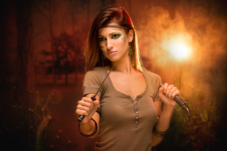 warrior woman: Portrait of a warrior woman with combat knife at sunset Stock Photo