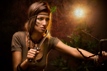 combat: Portrait of a warrior woman with combat knife at sunset Stock Photo