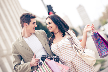 woman bag: Young happiness couple crossing the crosswalk, holding hands with a bunch shopping bags. Stock Photo