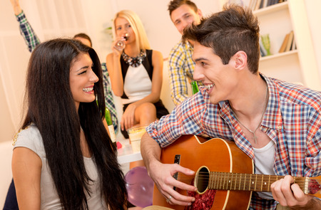 courting: A young man with an acoustic guitar, at home party, courting a pretty girl playing to her. In the background you can see young people sitting on the couch and enjoy the atmosphere of home party.