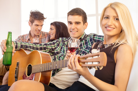 hang out: Small group of happy young people hang out at the house party with an acoustic guitar.