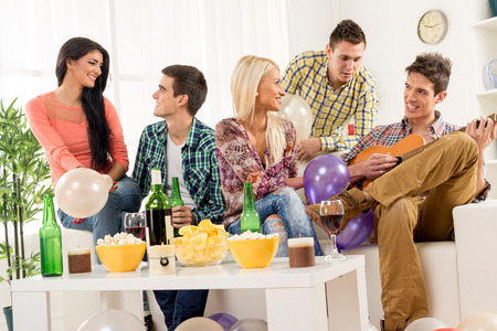 home interior: A small group of young people hang out at the house party, chatting with each other while their friend having fun playing acoustic guitar. Stock Photo