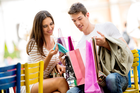 Girl and her boyfriend are resting after shopping in outdoor cafe with colorful chairs, watching with a smile in shopping bags, excited about the things they bought.