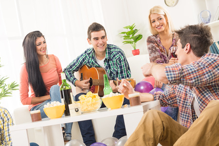 hang out: A small group of young people hang out at the house party, chatting with each other while their friend having fun playing acoustic guitar. Stock Photo