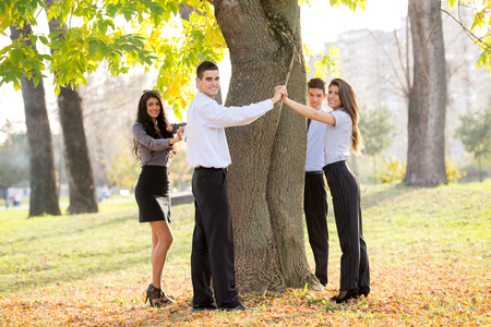 Group of young business people standing in a park hugging a tree trunk. photo