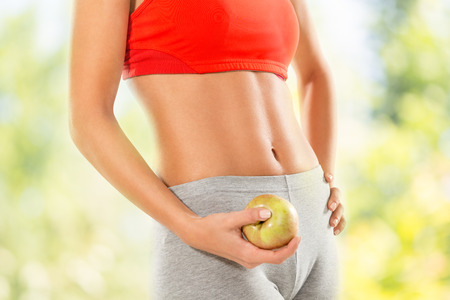 fit body: Close-up of a perfect woman body. Woman holding apple. Dieting concept.