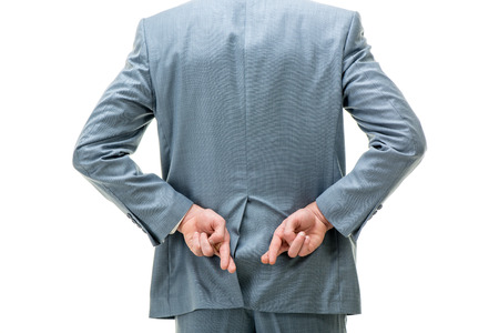 crossed fingers: Cropped of a businessman holding hands behind your back with crossed fingers. Stock Photo