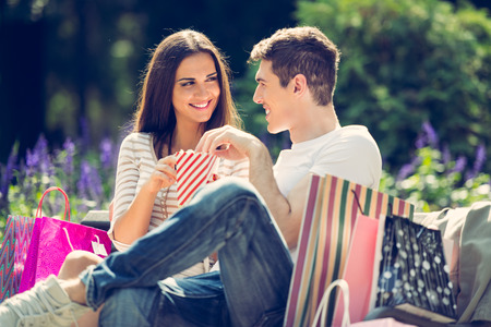 nibbling: A young loving couple resting on a park bench after shopping, enjoying the sun while nibbling popcorn.