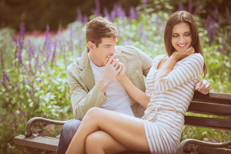 Milující mladý pár flirtovat, zatímco sedí na lavičce v parku. Reklamní fotografie