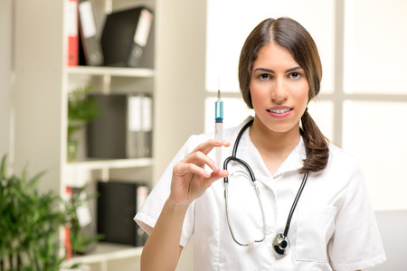 white coat: Pretty young nurse in a white coat, with a stethoscope over the neck holding an injection.