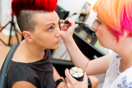 artist model: Make-up artist applying the basis for the shadow to model. Stock Photo