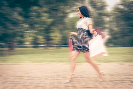after shopping: Cheerful young woman running in the park with many shopping bags after successful shopping. Stock Photo