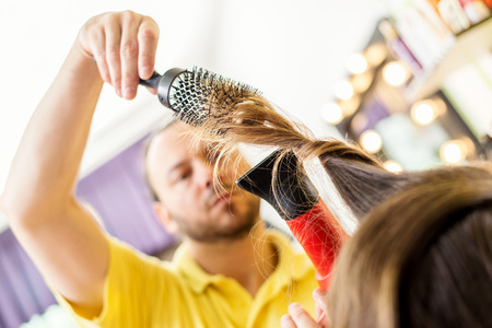 hair dryer: Man hairdresser drying long brown hair of a woman with hair dryer and round brush. Stock Photo