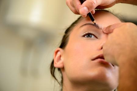 mujer maquillandose: Una mujer bonita que tiene ceja maquillaje aplicado por un artista de maquillaje. Acercamiento. Foto de archivo
