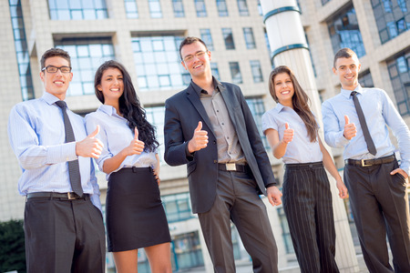 looking up: Young business team, elegantly dressed standing outside in front of office building with thumbs up. Looking at camera. Stock Photo