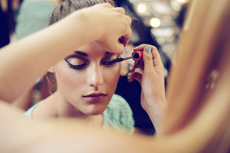 up: Make-up artist applying the mascara to model. Close up. Stock Photo