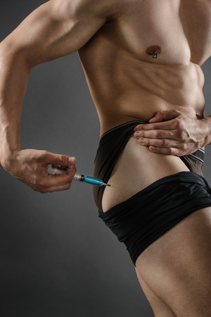 steroids: Close up of a muscular man injecting himself with steroids Stock Photo