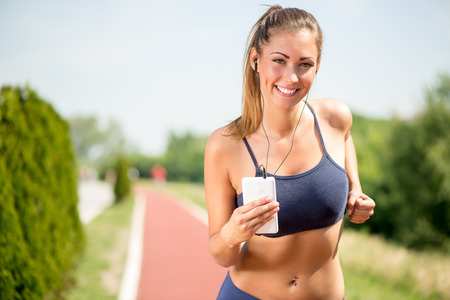 jogging track: Smiling girl running on the tartan track and listening music on headphones. Looking at camera.