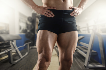 muscular build: Close up of strong muscular men`s legs in the gym.