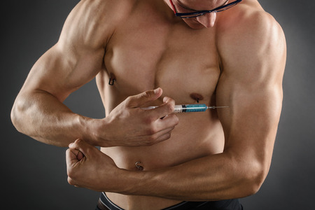 injection: Close up of a muscular man injecting himself with steroids Stock Photo