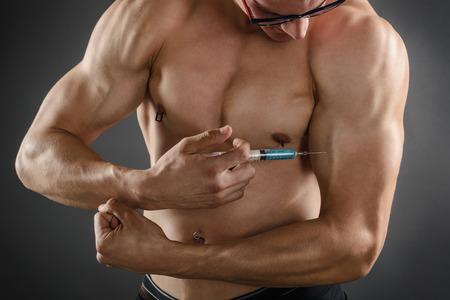 inyeccion: Primer plano de un hombre musculoso inyectarse con esteroides Foto de archivo