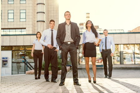 businesswoman suit: Young businessman, elegantly dressed with his hands in his pockets, standing proudly with his team of young businesswomen and businessmen in front of office building illuminated backlit sun.