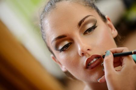 mujer maquillandose: Cerca de una maquilladora contornear los labios para modelar.
