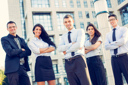businesswoman suit: A small group of young business people standing in front of office building with arms crossed and with a smile on their faces looking at camera. Stock Photo