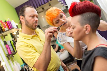 mujer maquillandose: Profesor de maquillaje ayudando formaci�n de los estudiantes para convertirse en artista de maquillaje