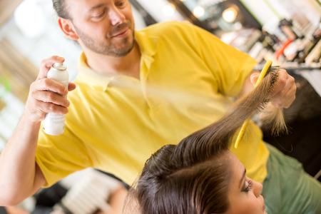 long brown hair: Man hairdresser spraying long brown hair of a customer woman.