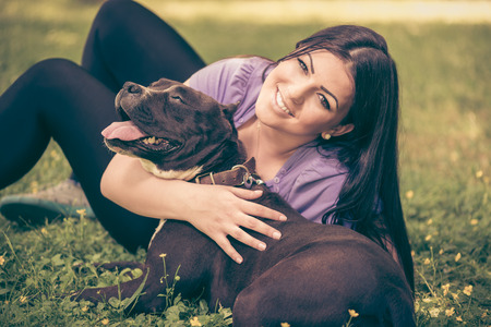 stafford: Beautiful young woman hugging her cute stafford terrier. They sitting on grass in the park and enjoying