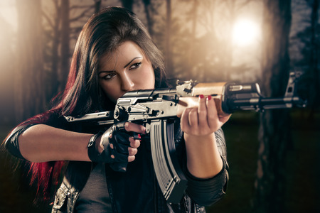 Attractive girl in forest standing in the attitude of aiming and looking through the sight automatic rifle.