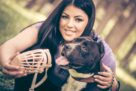 stafford: Beautiful young woman puts muzzle basket to her cute stafford terrier in the park .