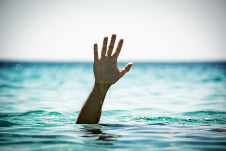 Single hand of drowning man in sea asking for help