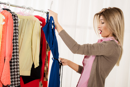 clothing store: Beautiful young shopper shocked by dress price tag.