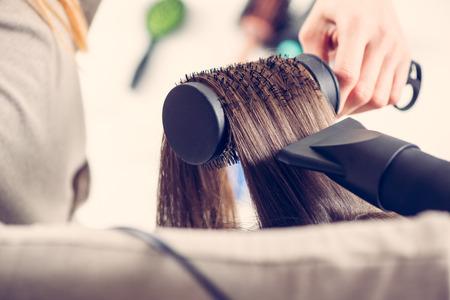 secador de pelo: Primer plano de un cabello marrón secado con secador y cepillo redondo.