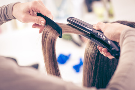Close-up of a hairdresser straightening long brown hair with hair irons.