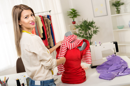 textile designer: Young woman, fashion designer, creates a dress on mannequin. Looking at camera.