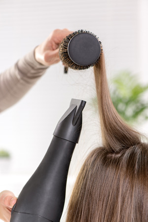 human hair: Close-up of a drying brown hair with hair dryer and round brush. Stock Photo