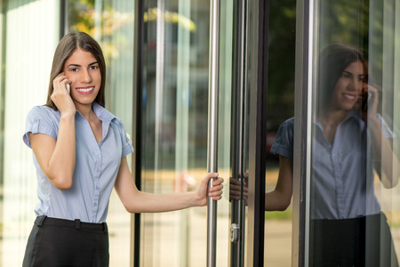 enters: Young beautiful business woman enters the office building and talking on mobile phone. Looking at camera. Stock Photo