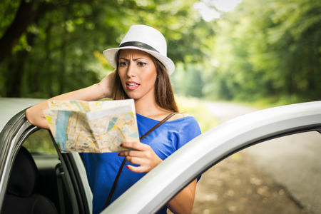 confusion: Confused lost beautiful woman standing leaning at car in the forest and worried looking a map. Stock Photo