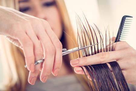 capelli lisci: Primo piano di un parrucchiere tagliare i capelli di una donna. Messa a fuoco selettiva.