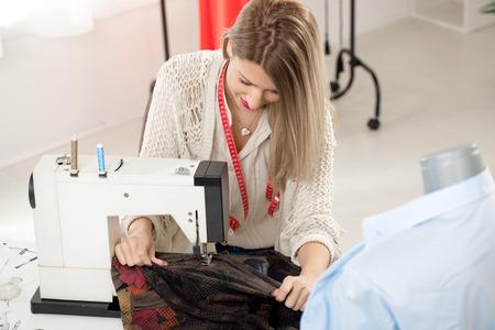 maquina de coser: Joven hermosa muchacha sonriente coser con una m�quina de coser.