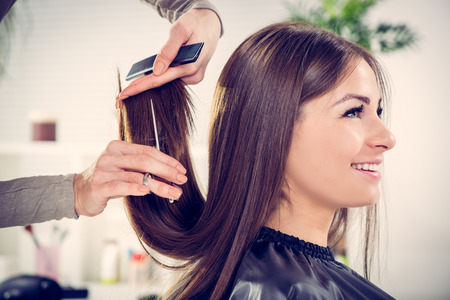 tijeras: Mujer hermosa joven después de haber cortado el pelo en la peluquería.