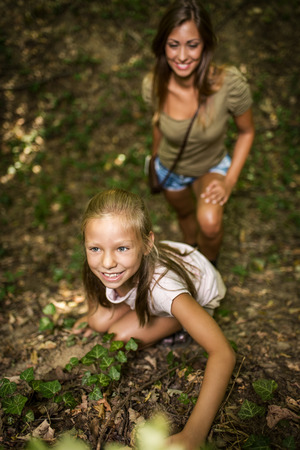 Beautiful young girl having fun in the forest. Mother looking in her.