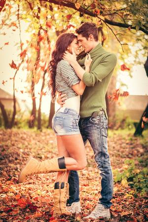 parejas romanticas: Pareja heterosexual joven en el amor en el parque, de pie sobre las hojas ca�das, apoyada la cabeza el uno al otro, mirando el uno al otro y sonriendo. Foto de archivo