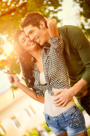 embraced: Young love couple in the park are embraced, a girl carries sprig of autumn leaves. Stock Photo