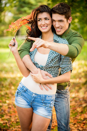 embraced: Young couple embraced in the park outstretched fingers of the hand pointing to something, while the girl carries in her hand a sprig of autumn leaves.