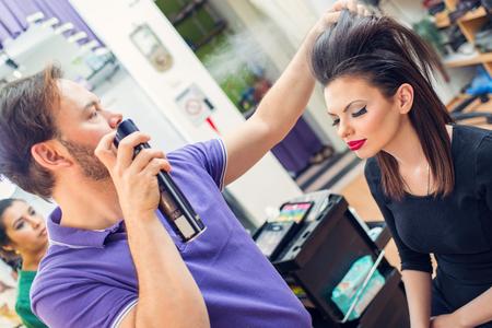 bouffant: Man hairdresser spraying long bouffant hair of a customer woman.