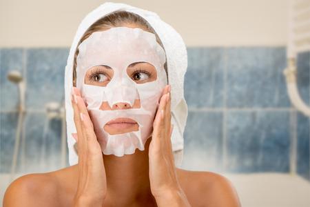 limpieza de cutis: Mujer joven hermosa que aplica la máscara facial cosmética en el baño. Foto de archivo